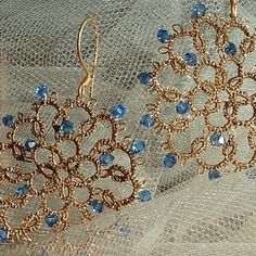Earrings tatted in gold thread with Swarovski crystals.