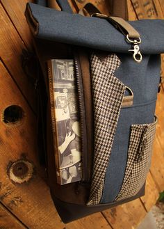 Brown & blue upcycled roll top rucksack with an extra opening -securing with zipper- on the front which gives the ability to access easily the inside of the bag without having to unroll it, by 'eating the goober'