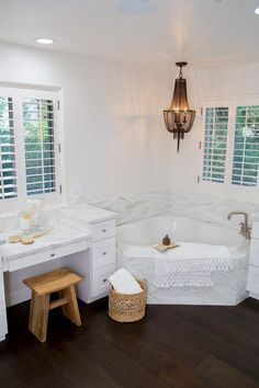 To give these homeowners the relaxing bath space they wanted, designers added a large corner tub encased in marble for elegance and durability. They also added a stylish chandelier for ambient lighting and a makeup table for an easier morning routine.