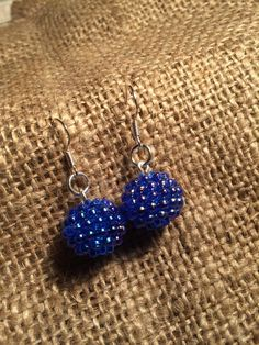 On fine silver ear pieces are shinny blue berries beads, made from resin.