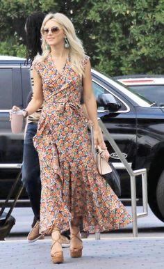 Julianne Hough wearing a floral wrap front maxi dress, lace up wedge sandals, mini beige satchel bag, oversized sunglasses, and green drop earrings