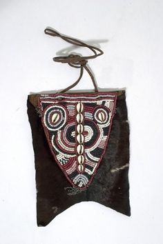 Buttock ornament made of hide, with dark brown hair, decorated with a central triangular beaded panel of glass beads forming circular motifs with a central column of seven cowries. Attached to the panel at all three corners are small metal chains.