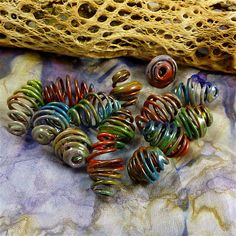 Such a cool idea!  What fun to form our own cage beads with heavy-gauge wire and roll them in a variety of different colored enamels, torch-fire them, and enjoy our own creativity.
