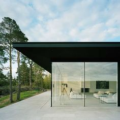 This house on a rocky hilltop in Sweden by Swedish architect John Robert Nilsson sits upon on a limestone-covered concrete plinth, which provides a continuous floor surface inside and outside of the house. The exterior of Villa Överby is finished in matte black, interrupted only by glass walls which provide views out towards the sea. The glass More