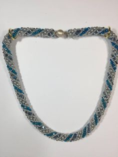 This 19 beaded necklace is woven in a stitch called Russian spiral. Three types of 4mm beads spiral, separated by a row of silver seed beads. The sterling silver clasp has a hidden safety tab that clicks into a 10mm round bead. The three types of 4mm beads used in this necklace are