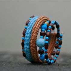 This unique coiled bracelet is full of different textures - soft crochet tube is accompanied by glass and wooden beads.