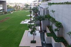 This luxury residential complex in South Mumbai includes a contemporary landscape design that combines water and flora, to create a dynamic and distinctive landscape.  A multipurpose lawn extends all the way from the avenue to the edge of the podium - a large expanse of green with a cricket pitch - ending in an abstract composition of cascading waterfalls.