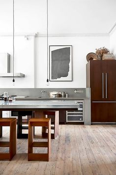 Modern kitchen with concrete countertops and bare wood floors