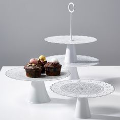 Give your baking a lift a top this two-tier tray. Metalworkers from India expertly cut each one, creating a delicate, scalloped edge before each is painted with a white and silver filigree design. By makers with Noah's Ark, a fair trade handicraft business in India.