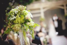 #aisle decor with tall pilsner vase with floral of white and green