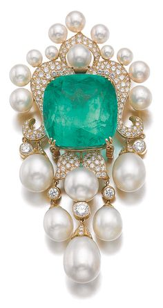 EMERALD, CULTURED PEARL AND DIAMOND PENDANT/BROOCH, AMR SHAKER Set with a cushion-shaped emerald weighing 104.97 carats, to a decorative mount highlighted with brilliant-cut diamonds and cultured pearls, suspending a similarly set fringe, signed Shaker, together with a gold chain measuring approximately 920mm.