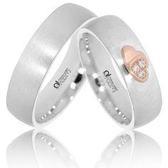 Un model deosebit de verighete din aur alb cu finisaje mat satinate. Modelul inelelor este unul simplu si elegant, pe inelul damei fiind dispuse doua inimioare unite din aur roz, cu trei cristale de zirconiu.