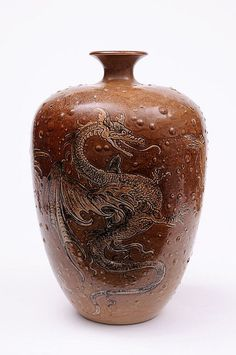 A Martin Brothers salt glazed stoneware vase of shouldered oviform with short flaring neck the blistered brown body sgraffito decorated with three dragons, a large wasp and other winged insects, 27cm high, the base incised Martin Bros. London & Southall, 10-1900, restoration to rim.