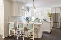A pair of white pleated pendant lights hang over a kitchen peninsula lined with…