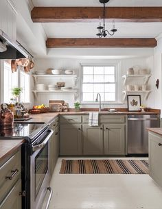 9 Essential Tips for Choosing the Coziest Farmhouse Kitchen Colors Even when the colors are cool, farmhouse kitchens are warm and inviting. Get the look with these top tips for nailing the perfect farmhouse kitchen color palette. Sage Green Kitchen, Green Kitchen Cabinets, Kitchen Cabinet Colors, Painting Kitchen Cabinets, New Kitchen, Kitchen Cabinets And Open Shelving, Natural Wood Kitchen Cabinets, Island Kitchen, Kitchen Hacks