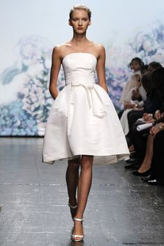 Monica Lhuillier's Lili. Silk white silk faille strapless 1/2 moon natural waist bodice with low V-back and box pleated high-low mini skirt.