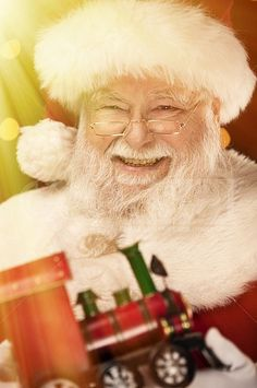 A real authentic Christmas photo of Santa Claus happy about giving a toy train as a gift. Real Santa Pictures and This images can be licensed to use at realsantaimages.com | Do Not Use Without A License