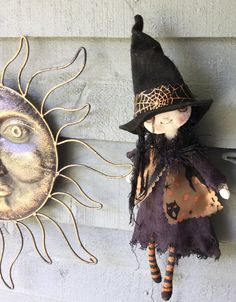This sweet witch is about 13 inches . She is hand made and hand painted with wired arms and orange eyes . Her Dress is made of hand dyed off black tobacco cloth . Her overdress is a neat vintage sheer fabric decorated with spooky cats. It is fastened with a tinselled ball . Her hat is hand made from black felt and decorated with a spider web ribbon . She would be a great gift for a Witch and Halloween collector . Suzie Hayward original