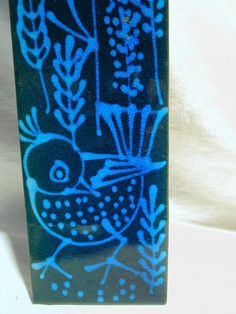 This Bo Melander Danish pottery tile plaque features a handpainted 1960's modernist bird and floral in Egyptian blue against a black ground. The back is stamped Bo Melander Danmark