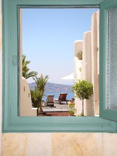Santorini, Greece..I want to be walking thru this door to those chairs....