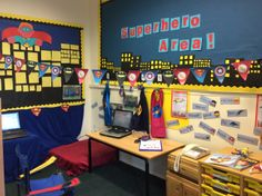 Superhero area with numbered cloaks, gadgets, phones, emergent writing, word bank and photos of children engaged in play at Springmead School, Beckington, Somerset.
