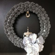Sweet gum seed pods glued to a foam wreath & spray painted silver.