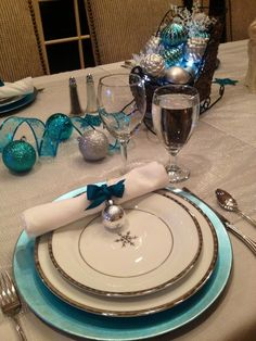 Pretty aqua charger with white snowflake plates. Table setting for Christmas