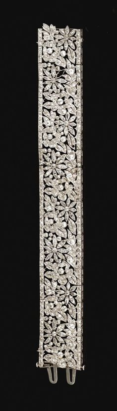 DIAMOND BRACELET, FRENCH, CIRCA 1915. The articulated open work band decorated with floral and foliate motifs, millegrain-set with triangular, circular-, step-cut and marquise- shaped diamonds, to an engraved gallery, mounted in platinum. French assay and maker's marks. #diamondbracelets