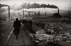 A man walks towards the chimneys of the steel foundry in West Hartlepool, England.