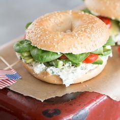 Sesambagel bestrichen mit Kräuterfrischkäse und belegt mit Tomaten, Avocado und Babyspinat - fertig ist das perfekte Frühstücks-Sandwich im Kringelformat.
