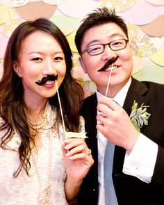 Mustaches from Paper Source were backed with thick paper and attached to sticks by the bride. A backdrop of scalloped fabric cutouts connected the self-service photobooth to the color palette of the wedding. Other fun props -- namely, a tiara and a veil -- were on hand for guests to use to pep up their snapshots.
