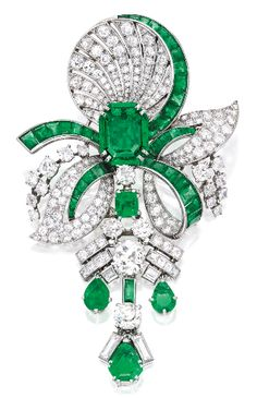 An Art Deco Platinum, Emerald and Diamond Pendant-Brooch, Mauboussin, circa 1935. The stylised bow suspending an articulated pendant, centred by an emerald-cut emerald, accented by pear-shaped, fancy and square-cut emeralds, the pendant set with one old mine-cut diamond and one old European-cut diamond, further set with round, baguette and square-cut diamonds and calibré-cut emeralds, signed Mauboussin, Paris, with French assay and workshop marks. #Mauboussin #vintage #brooch
