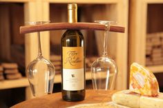 This piece slips over the neck of a bottle of wine and with notches on each end it elegantly supports two wine glasses. Makes for a perfect gift! Fits standard 1 1/4″ neck size wine bottle. http://www.katybarrelcompany.com/product/glass-holder-3/