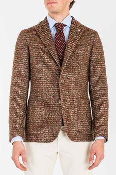 <p>Stile New Formal per la giacca decostruita a due bottoni con tasca a toppa e spacchi laterali firmata dalla sapienza di Tagliatore. Tessuto effetto shetland. La spilla a forma di cappello a cilindro