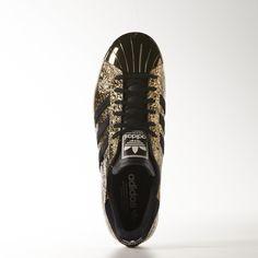 Denna guldskimrande adidas Superstar sko är inspirerad av boxningsmästarnas bälten. Skon är gjord i veckat, guldfärgat skinn med en metallicfärgad snäcktå som en hyllning till adidas boxningsarv.