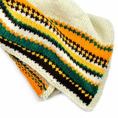 A cozy lap blanket just the perfect size for working at your desk, sitting on the couch, or keeping your little tot toasty warm. Features a green, yellow, and brown Scandinavian-style design on both ends and a cream background.