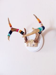 Bright, fun, and ready to pop on your wall! Serape Style Yarn Bombed Mounted Antler, unique, one of a kind, and ready to hang in your home! Matched to that of a traditional Mexican Serape Blanket. Our most popular Yarn Bomb Style! This antler has 3 spikes on each side and is mounted on a bright w...