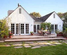 Before-&-After Backyard Makeovers French doors lead to a new flagstone patio that accommodates an outdoor eating area with room to spare. Flagstone pavers draw the eye into the grassy backyard, and lush greenery invites year-round relaxation. Outdoor Patio Pavers, Flagstone Pavers, Patio Steps, Backyard Patio, French Doors Patio, French Patio, Backyard Retreat, Backyard Makeover, Back Patio