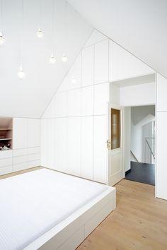 V této podkrovní ložnici bylo třeba vše přizpůsobit tvaru skosených stěn, aby se mohl celý prostor co nejefektivněji využít. Šikmé tvary se tak staly hlavním designovým prvkem celého projektu. Naprostou většinu nábytku tvoří bílé lamino pečlivě lemující okraje zdí a stropu. Úložné prostory jsou pak precizně zasazeny těsně vedle sebe. Tvoří nádherný jednolitý celek, který je narušen jen tehdy, když některá dvířka otevřete. Také postel je tvarována do jednoho bloku. Divider, Room, Furniture, Home Decor, Bedroom, Decoration Home, Room Decor, Rooms, Home Furnishings