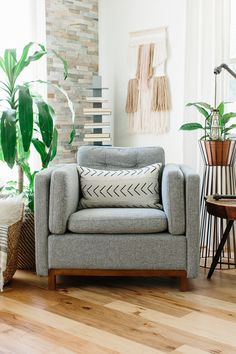 gray wool arm chair with white and black mud cloth pillow and pastel wall  hanging Living b5f50cf708e