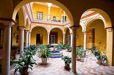 This is what I want my social club's courtyard to look like! Stock Photo #1890-35713, Typical riad style house now converted into Hotel Las Casas de la Juderia, Santa Cruz district, Seville, Andalusia.