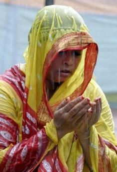 A woman prays in the rain in Dhaka, Bangladesh, September 29, 2006.