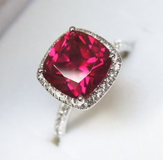 Beautiful ruby red ring framed by a halo design and a pave style band. A good start and it needs some exceptional skinny rings to make it  look even for amazing.