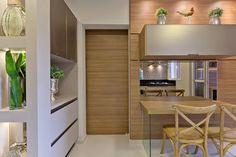Cozinha com mesa para refeições rápidas, basculante superior e espelho bronze, para dar leveza pé em vidro. Nichos na lateral do armário pra completar a decoração.