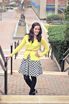 Cute polka-dotted dress with black tights and yellow cardigan.