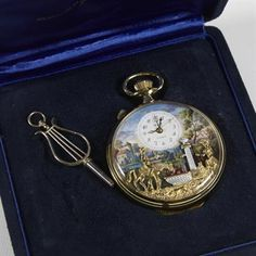 Lot 209: An automata musical alarm pocket watch by `Reuge`, circa 1960, comprising 17-jewel lever movement with attached pinned cylinder movement, coloured printed scene of a landscape with a lady at a water pump facing a horse & rider at the water trough, rider with a bird on his arm; complete with ornate shaped original key & in original fitted box. Estimate £50 - £80. Sale date 17th June 2014 www.afbrock.co.uk