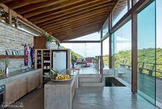 Cozinha contemporânea com uma bela vista e uma grande bancada de cimento contraste com o telhado de madeira