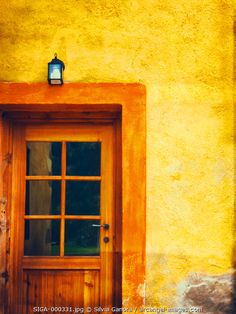 Wooden door with glass and tiny lamp over it. Yellow, saturated wall - ©Silvia Ganora Photography - All Rights Reserved  #bookcovers #doors #architecture #yellow