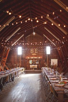 Barn wedding. Love the lights and initials and banquet tables
