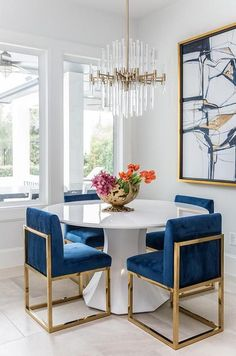 A round white dining table finished with gold and blue sapphire dining chairs under a brass and lucite chandelier.Get inspired by these dining room decor ideas! From dining room furniture ideas, dining room lighting inspirations and the best dining r